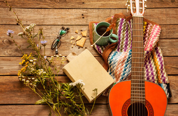 Late summer or autumn relaxation, rustic background on wood from above. Country lifestyle, rural vacation or agrotourism concept. Book, blanket, coffee and classic guitar.