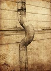 Textured verdigris rain pipe pointing right.