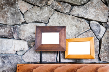 Stone fireplace wall close up with two empty picture frames on wood mantle