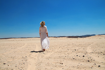 Girl in white dress walking in desert