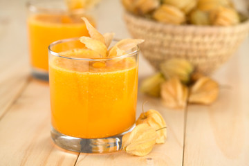 Freshly prepared juice made of physalis (lat. Physalis peruviana) served in glass (Selective Focus, Focus on the front of the glass rim)
