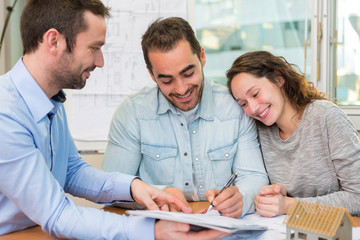 Young attractive people signing cotract with meeting real estate