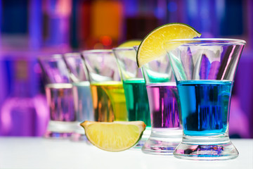 Long perspective row of shots with color drinks