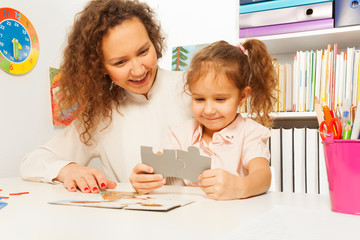 Portrait of teacher and girl holding puzzle pieces