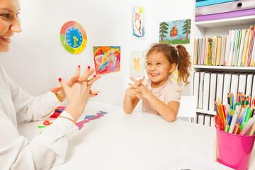 Smiling girl doing finger exercises as her teacher