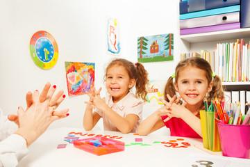 Two girls doing finger exercises as her teacher