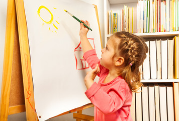 Cute girl painting brush watercolors on a easel