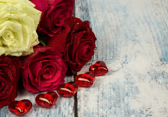 Five roses and red hearts on a background of a wooden tabletop i
