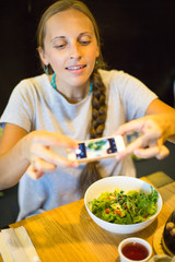 Woman taking a photo of salad with smartphone