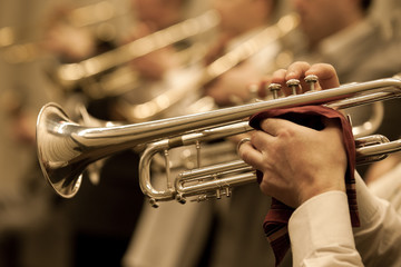 The trumpet in the hands of a musician in the orchestra closeup