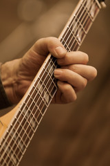 A man's hand on the strings of a guitar closeup