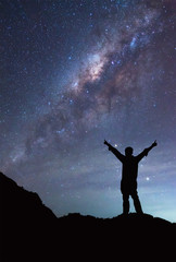 A person is standing next to the Milky Way galaxy spread hand on
