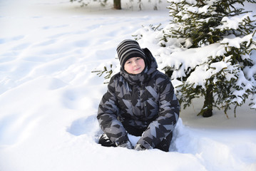 Teen boy sitting on   snow in the winter forest