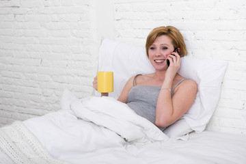 young beautiful girl having coffe on bed while watching internet news in his mobile phone in online communication