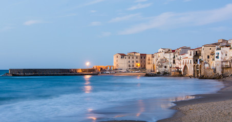 Beautiful view at calm city beach in Italy, Cefalu at sunset