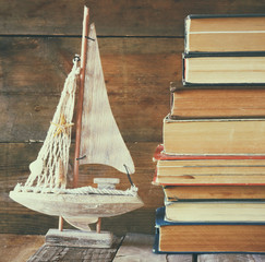 stack of old books next to decorative sailing boat wooden table. vintage filtered image