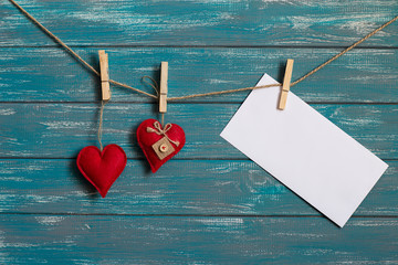two red hearts and envelope are hanging on the rope on the blue wooden background