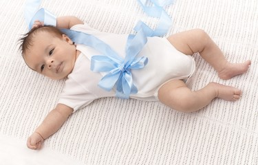 Baby boy in bodysuit and blue ribbon