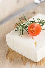 Schafskäse mit Rosmarin und Tomaten auf einem Holzbrett