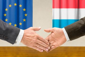 Vertreter der EU und Luxemburgs reichen sich die Hand