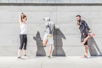 On a sunny day, a three friends in sportswear does stretching outdoors near a building