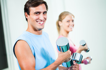 Couple exercising in gym, using weights