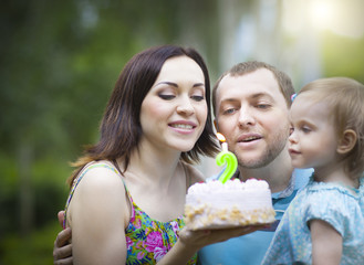 Happy family celebrating second birthday of baby daughter