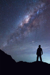 A person is standing and seeing Milky Way galaxy on night sky.