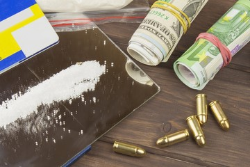 Sales of drugs. International crime, drug trafficking. Drugs and money on a wooden table. The concept of trafficking.
