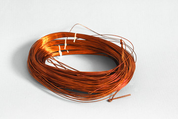 Skein cooper wire on white background. Copper wire winding, coil, spool section of the electric machine - generator or motor