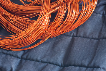 Windings of Copper Wire on a dark background textile. Winding, coil, spool of electrical machines - generator or motor