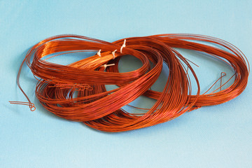 Skein copper wire on light blue textured background. Copper wire winding, coil, spool section of the electric machine - generator or motor