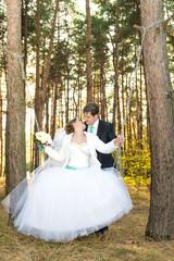 Groom rolls bride on a swing in the woods