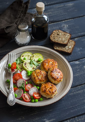 Chicken cutlets,  grilled zucchini  and fresh vegetable salad on a dark wood background