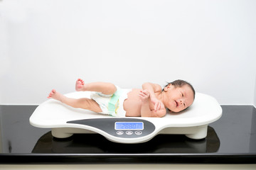 Asian newborn baby laying on the scales