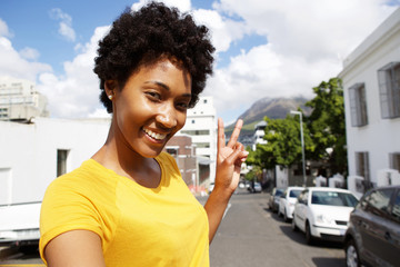 Smiling young woman gesturing peace sign