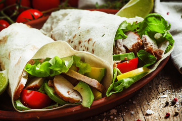 Fresh roll shawarma (doner) with meat, avocado, cherry tomatoes,