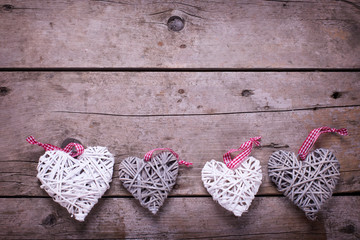White and grey  decorative  hearts on  aged  wooden background.