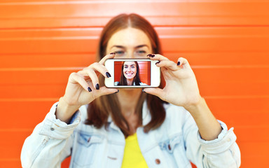 Closeup woman makes self-portrait on smartphone, view of screen