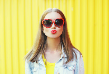 Portrait pretty young woman in red sunglasses blowing lips kiss