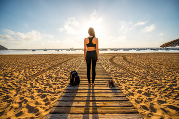 Woman in black sport clothes standing on the beach