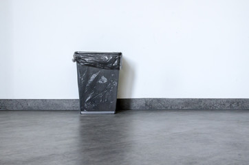 Empty rubbish basket on black floor and white wall behind
