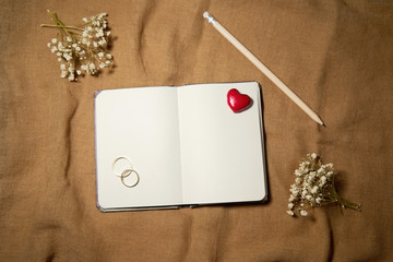 Blank notebook with heart and wedding rings on sackcloth backgro