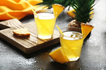 Glasses of pineapple juice on a black wooden table
