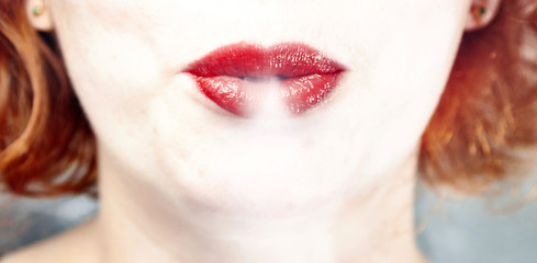 Red lips woman blowing out smoke