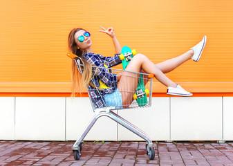Fashion cool girl having fun sitting in shopping trolley cart wi