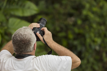 Male photographer captures a bird photo in the rain forest