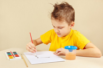 Little boy in a yellow shirt painting colors