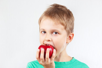 Little boy in a green shirt eating a red apple