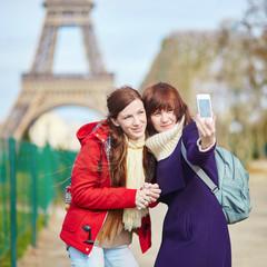 Two cheerful beautiful girls in Paris taking selfie